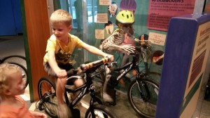 Child biking next to a skeleton biking too.