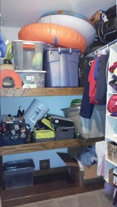 A closet, organized but filled to the ceiling with things.