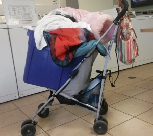 A stroller with a plastic bin sitting on the chair filled with laundry.