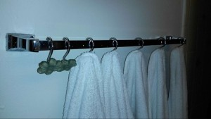 Decorative shower curtain hooks over the towel bar holds up to six towels.