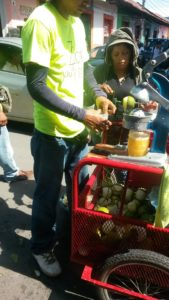 Nicaraguan street vendor selling fresh squeezed orange juice.